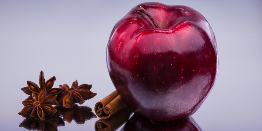 Красное блестящее яблоко с корицей