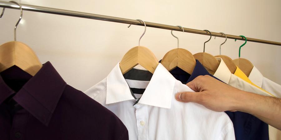 Мужчина вынимает белую рубашку из гардероба