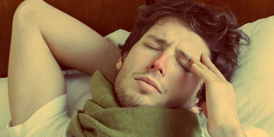 Больной мужчина в шарфе лежит на кровати
