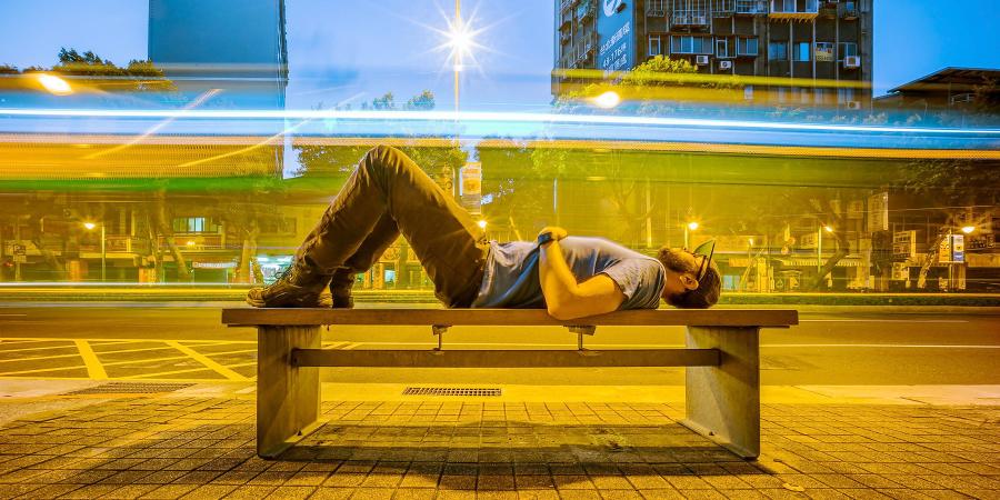 Мужчина, спящий на лавочке перед дорогой