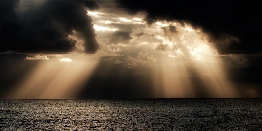 Солнечные лучи сквозь чёрные тучи над морем