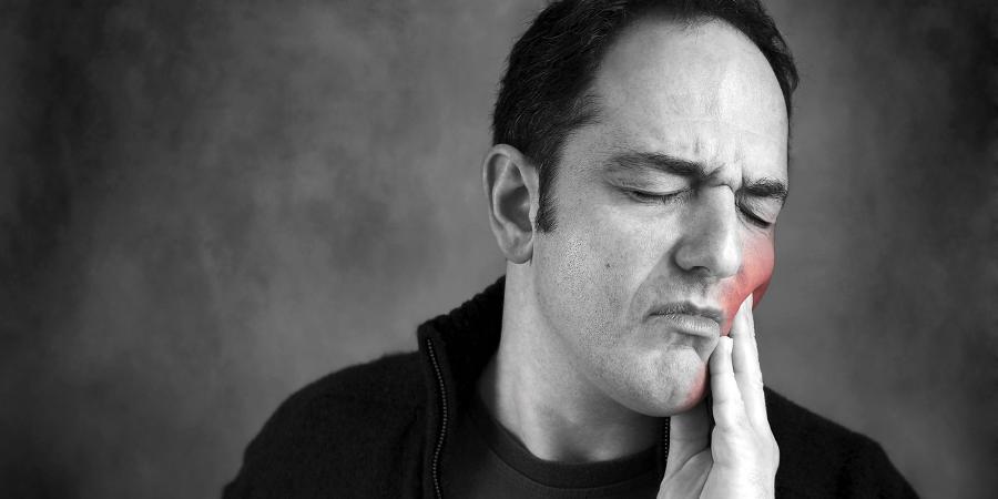 Мужчина, страдающий от зубной боли