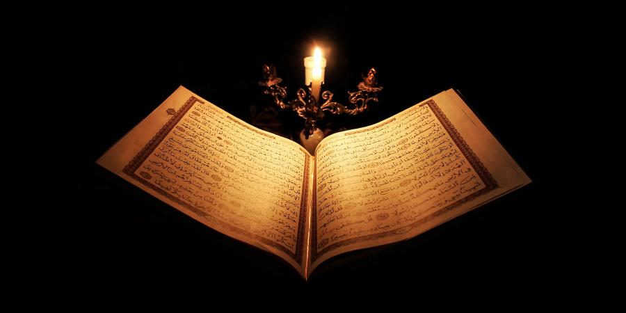 Горящая свеча над раскрытым Кораном
