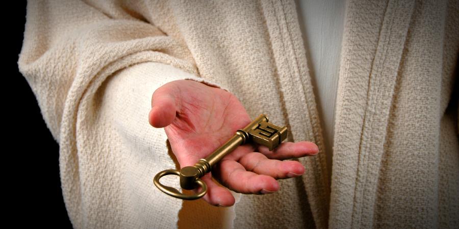 Мужчина в белом одеянии с ключом в руке