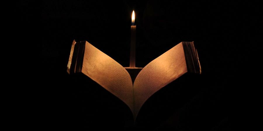 Раскрытая книга на арабском под горящей свечой