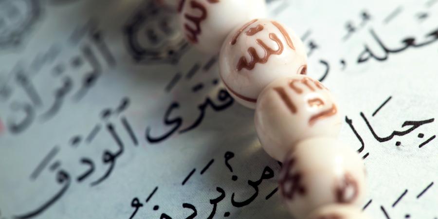 Чётки с именем Аллаха на странице Корана