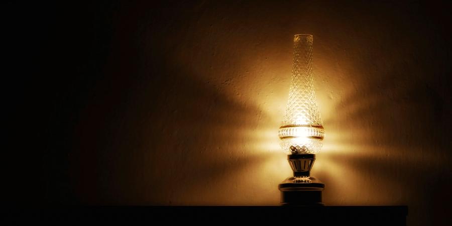 Зажжённая старинная лампа на столе