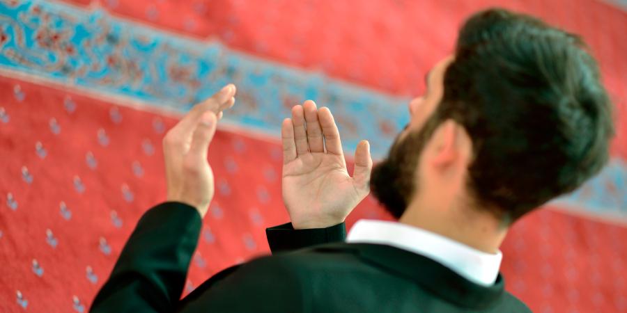 Мусульманин в костюме читает дуа в мечети
