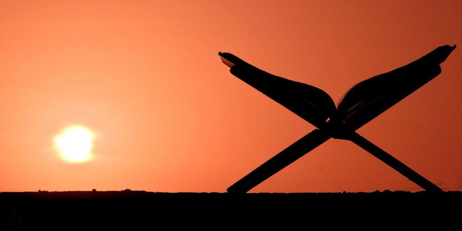 Коран на подставке на фоне восходящего солнца