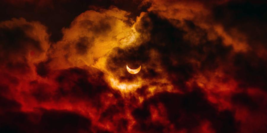 Солнечное затмение за красными облаками