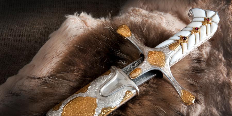 Богато украшенная сабля с белой рукоятью в ножнах на шкуре животного