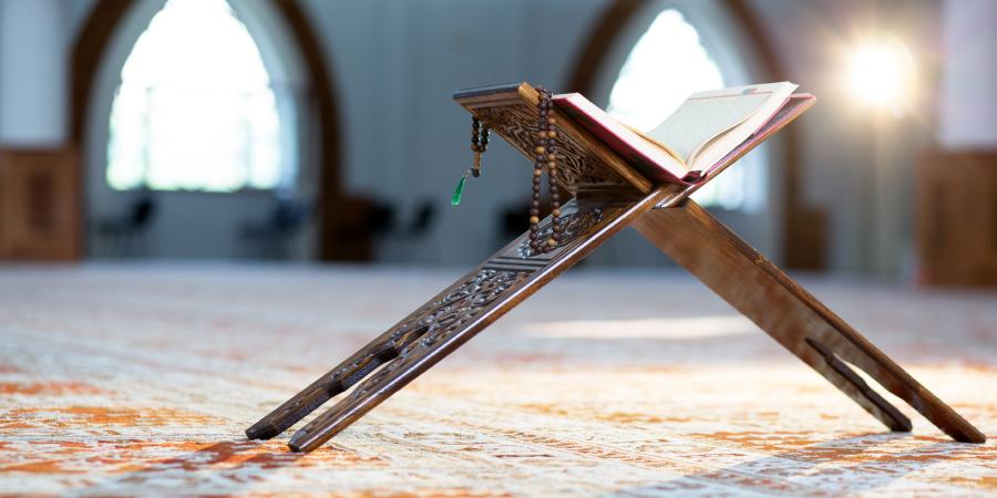 Коран и чётки на деревянной подставке посреди мечети