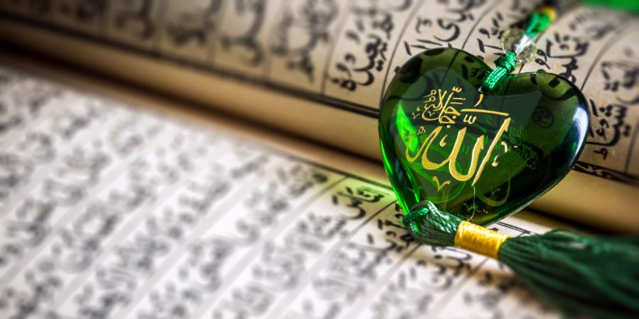 Зелёные чётки с именем Аллаха, лежащие на открытом Коране