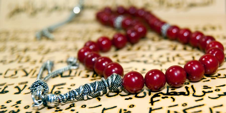 Красные чётки на открытом Коране