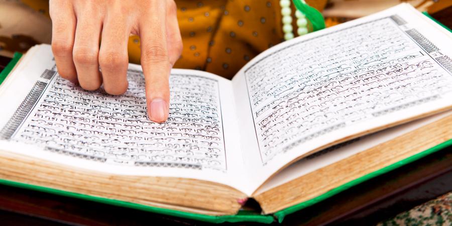 Мужчина, читающий Коран с чётками в руке