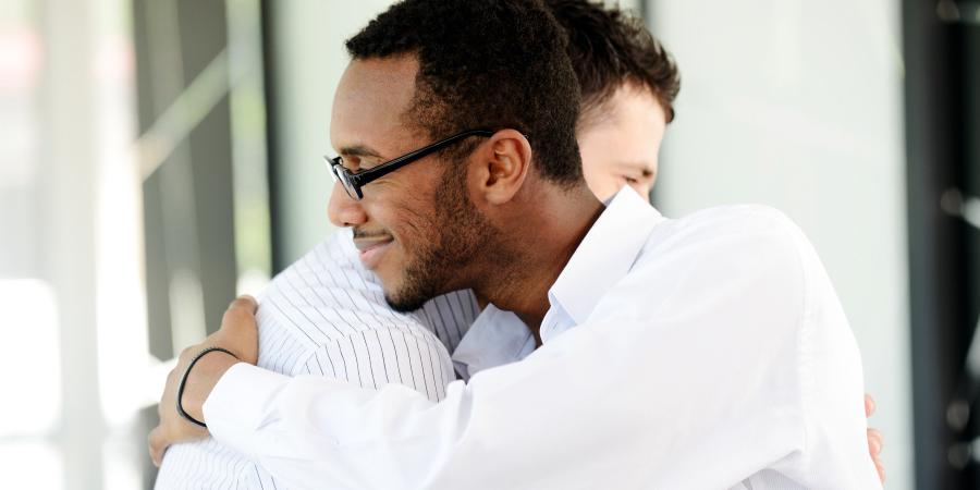 Обнимающиеся мужчины в белых рубашках