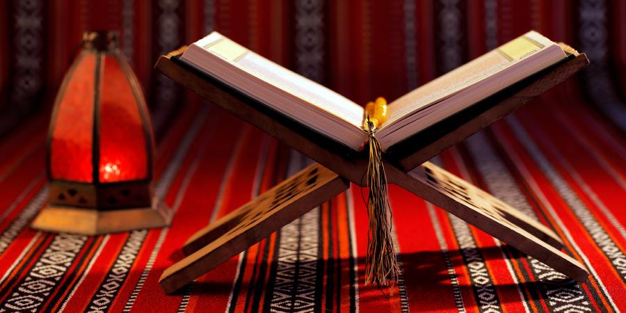 Открытый Коран на деревянной подставке рядом с красной лампой