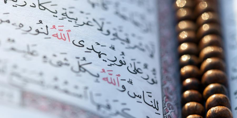 Страница Корана с лежащими на ней чётками