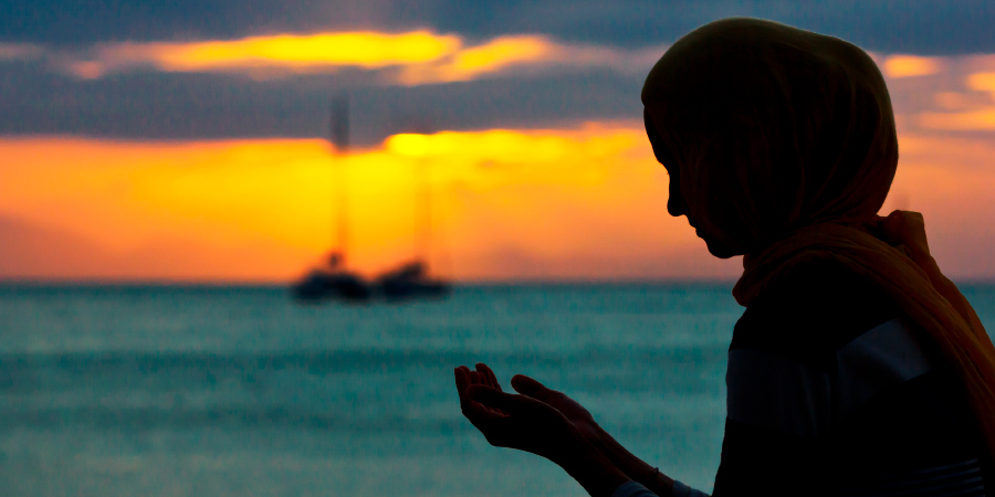 Мусульманка молится на закате на берегу моря