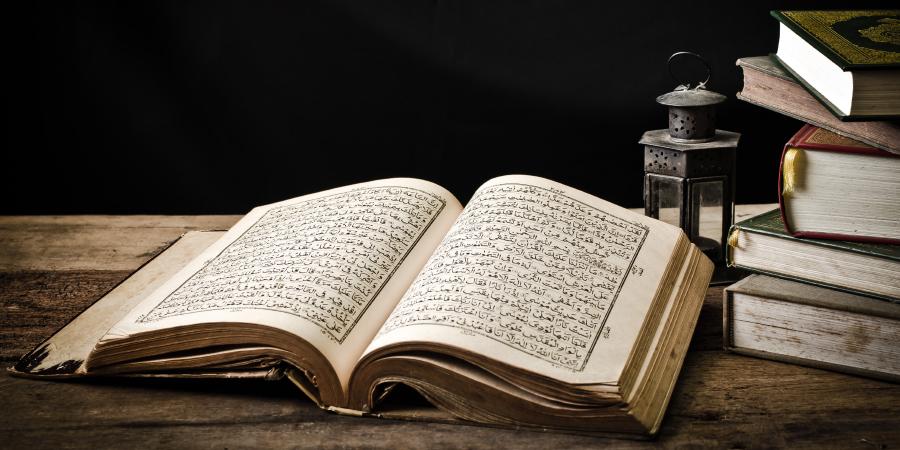 Открытый Коран и исламские книги на деревянном столе