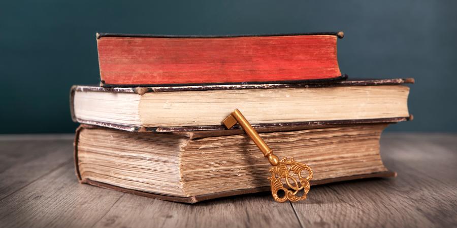 Золотой ключ и стопка старых книг на деревянном столе
