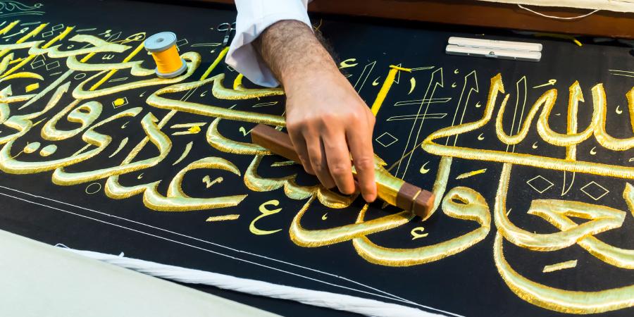 Мужчина, вышивающий золотые аяты Корана на чёрной материи, Путраджая, Малайзия