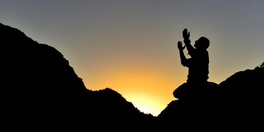 Силуэт молящегося мужчины