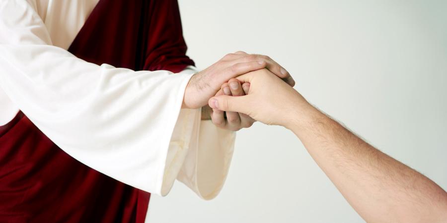 Человек в красно-белом одеянии держит мужчину за руку