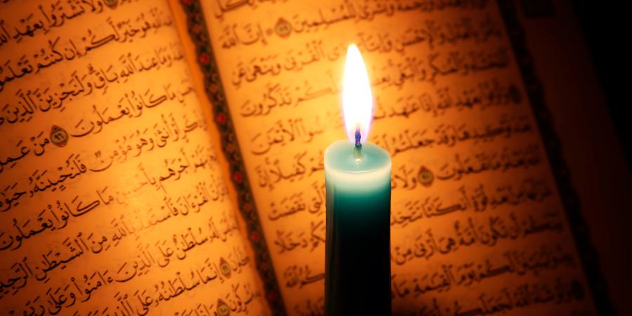 Горящая свеча перед открытым Кораном