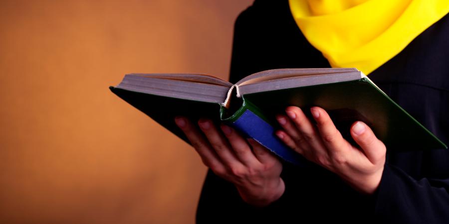 Мусульманка в жёлтом хиджабе читает книгу