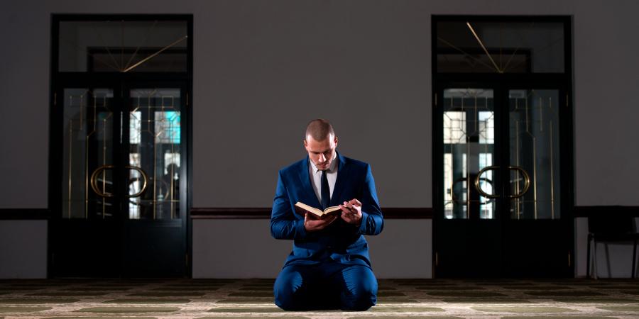 Мужчина в синем костюме читает Коран в мечети