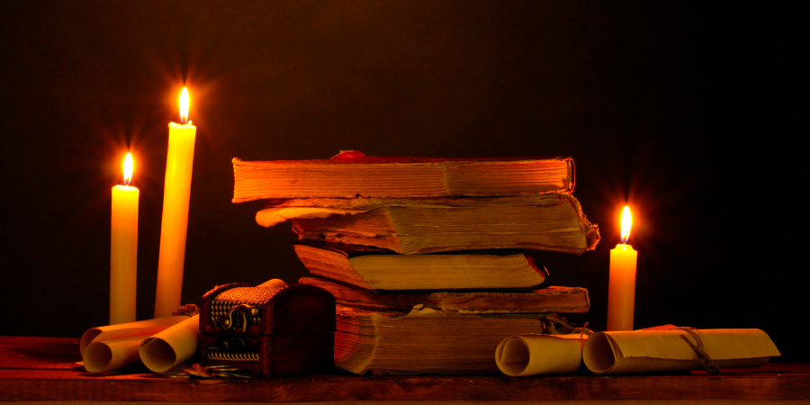 Стопка старых книг, свитки и горящие свечи на деревянном столе