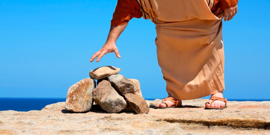 Мужчина, тянущийся за камнем