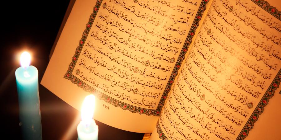 Две горящих свечи перед открытым Кораном