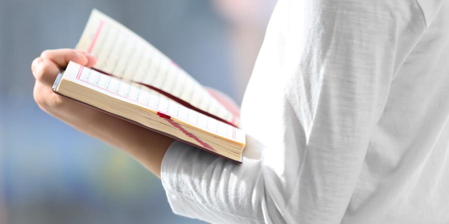 Мужчина в белом держит открытый Коран
