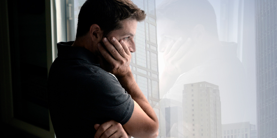 Грустный мужчина смотрит в окно