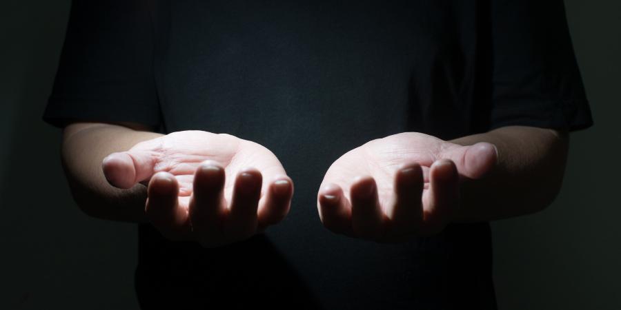 Мужчина, протянувший руки в молитвенном жесте