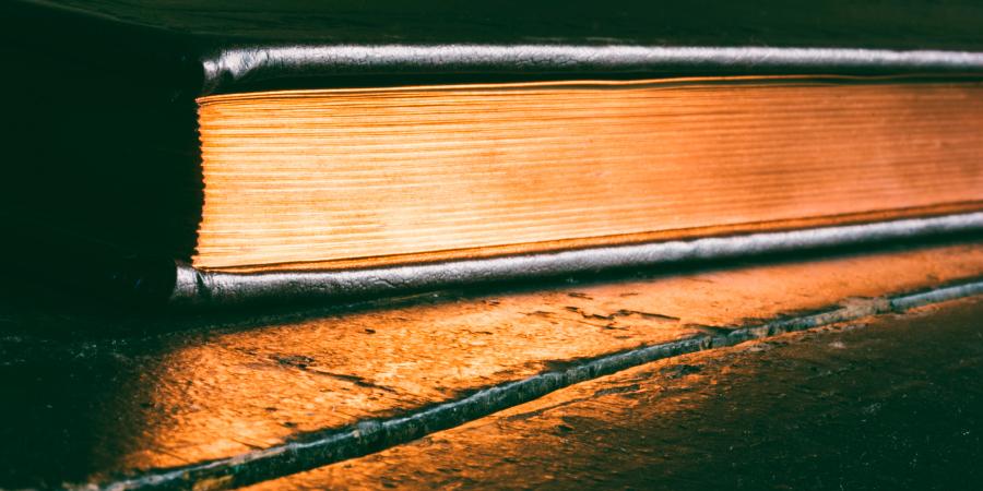 Закрытая книга с золотыми страницами на деревянном столе