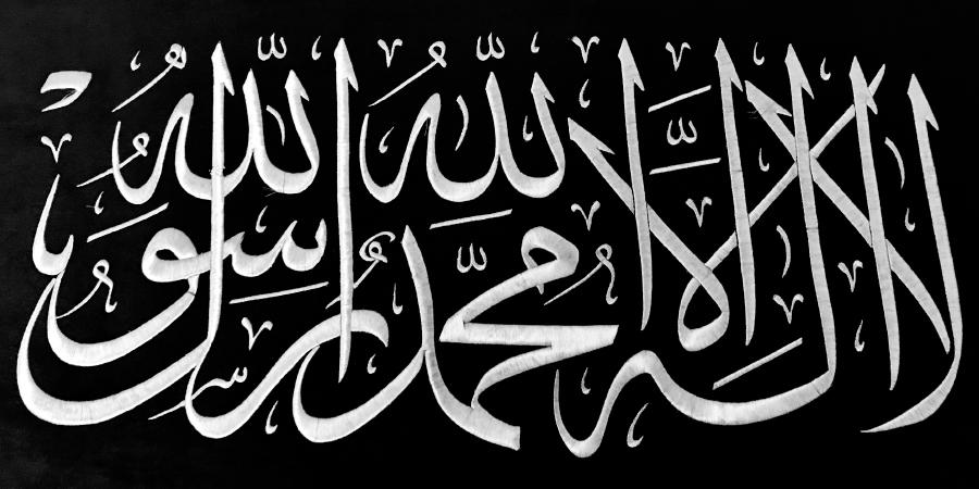 Свидетельство веры (шахада), вышитое белыми нитками на чёрном фоне