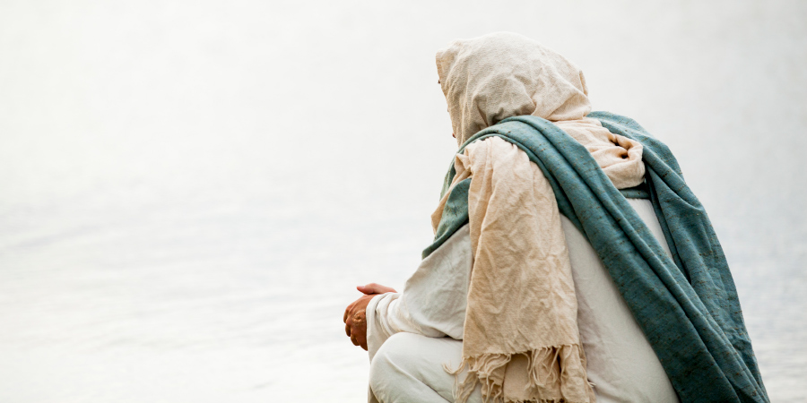 Человек в белом капюшоне, сидящий возле воды