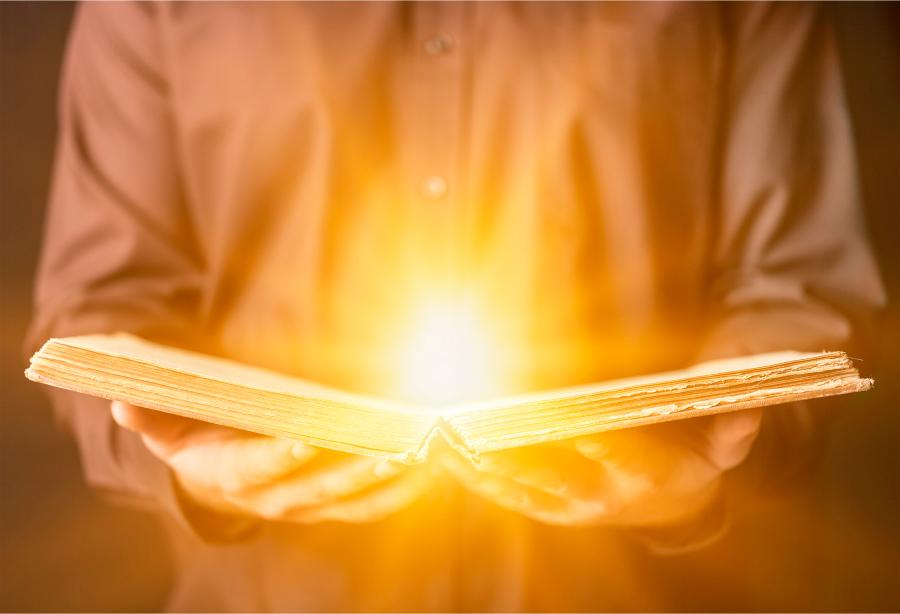Мужчина, держащий в руках открытую книгу, из которой исходит свет