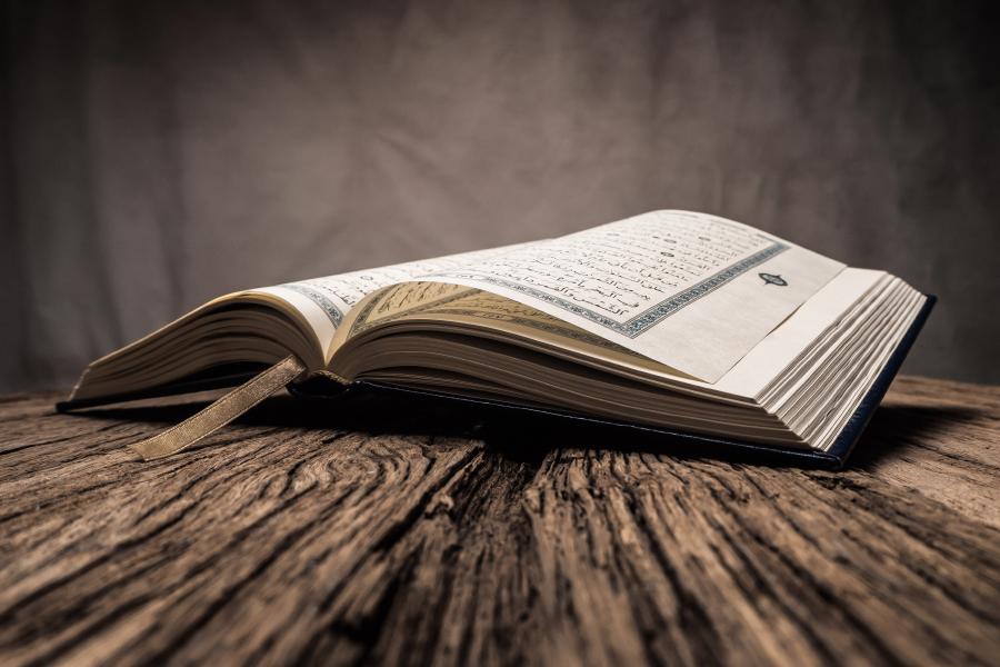 Открытый Коран на деревянном столе