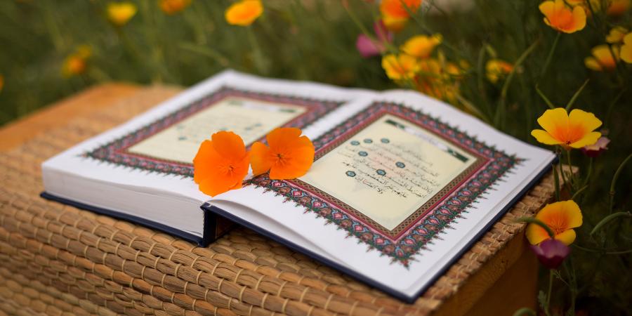 Открытый Коран в окружении цветов
