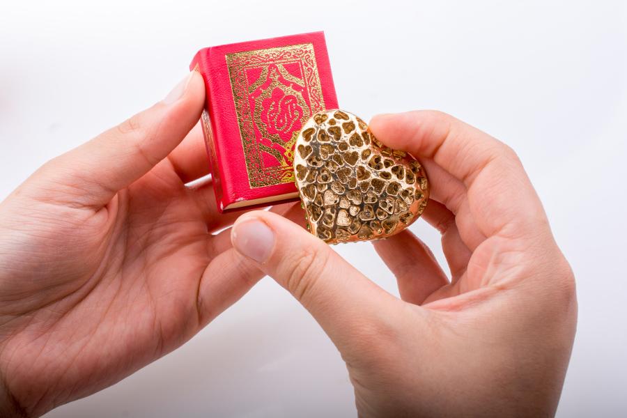 Руки, держащие миниатюрный Коран и золотое украшение в виде сердца