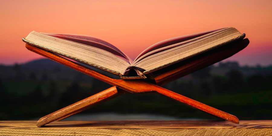 Коран на деревянной подставке на фоне природы