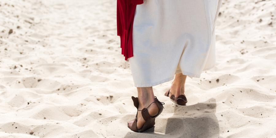Человек в сандалиях, идущий по пустыне