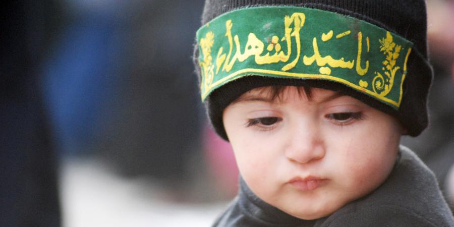 Маленький шиит с повязкой на голове с надписью «Йа сеййид аш-шухада!» («О господин мучеников!»)