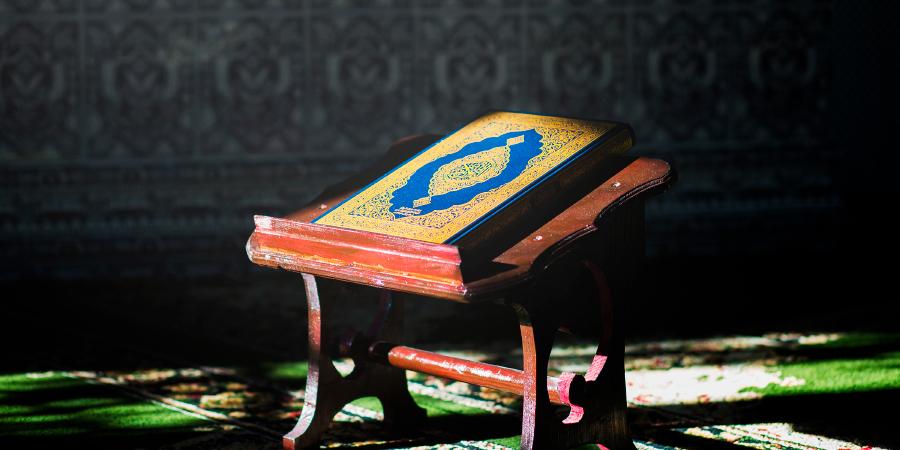Синий Коран на деревянной подставке