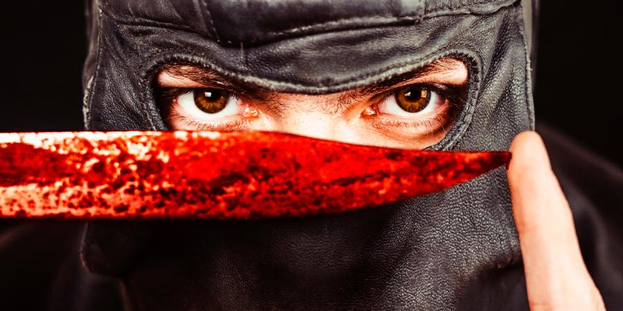Террорист в маске показывает окровавленный нож