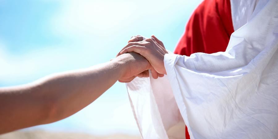 Мужчина в бело-красном одеянии сжимает руку другого человека